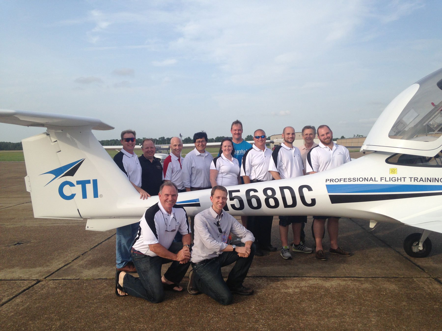 Group of airport team in front of a small blue and white airplane at NQA Airport
