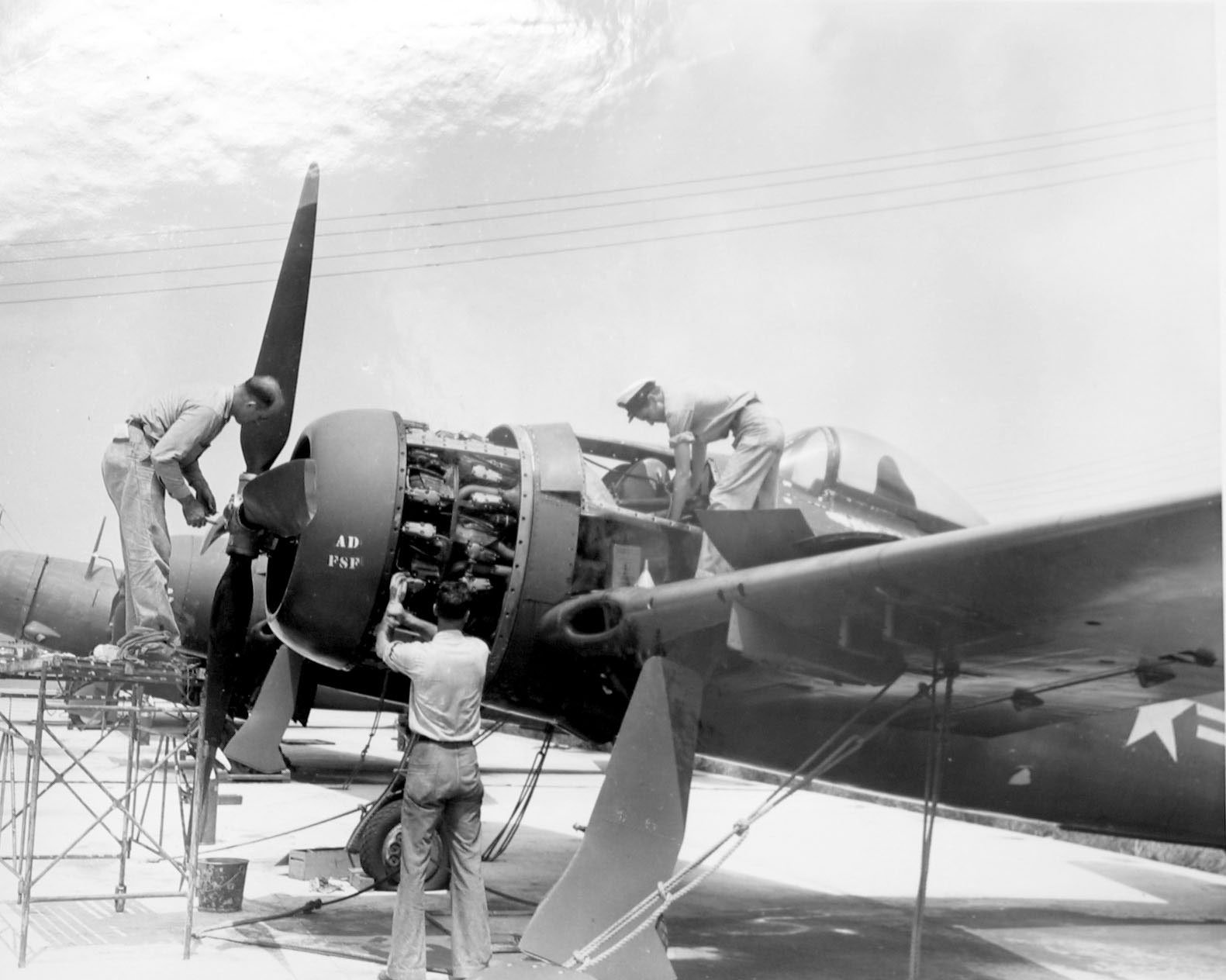 Old image of mechanics working on a single engine aircraft at the Memphis MIllington Airport