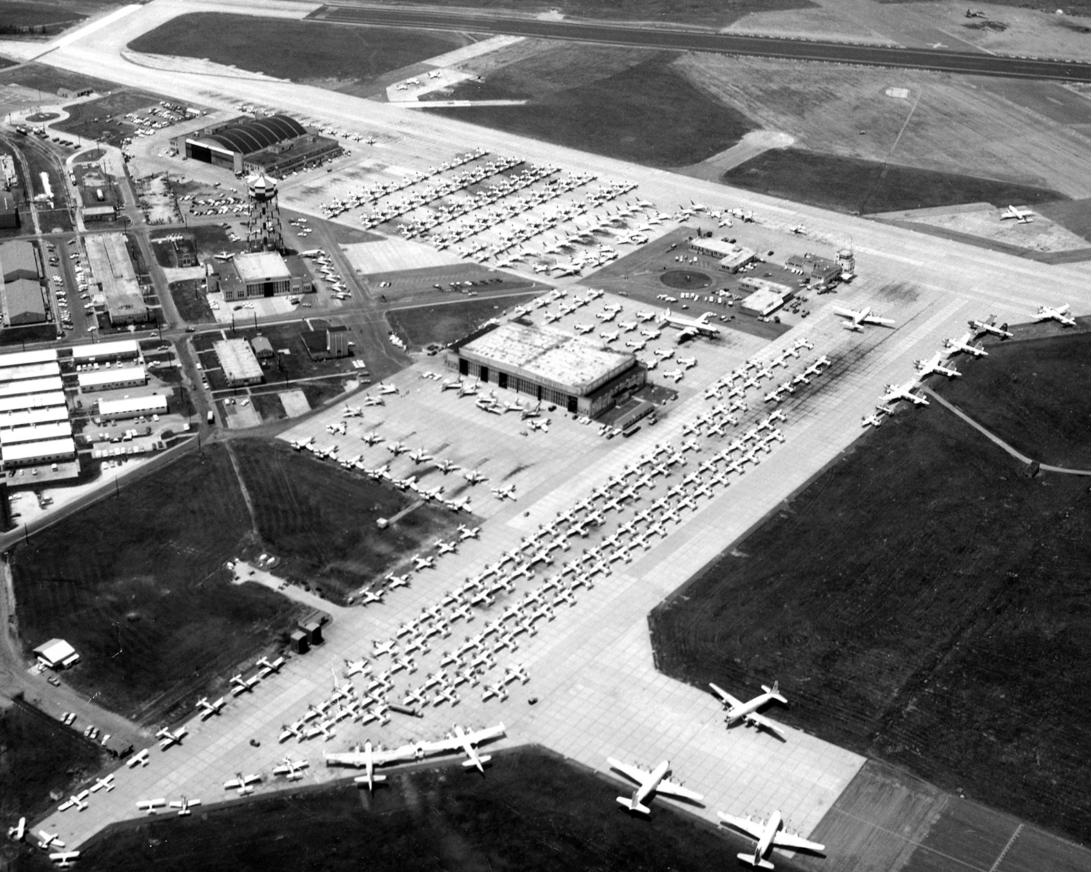 Black and white image of the large Memphis Millington Airport Ramp full of small airplanes
