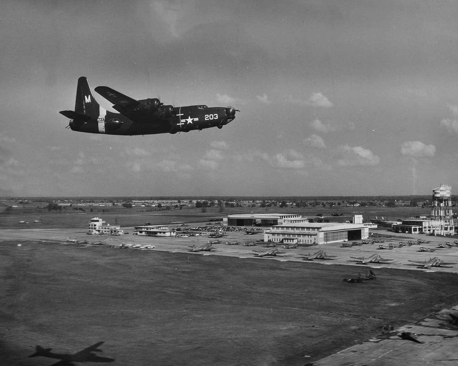 Black and white image of a old vintage four engine aircraft flying over NQA airport