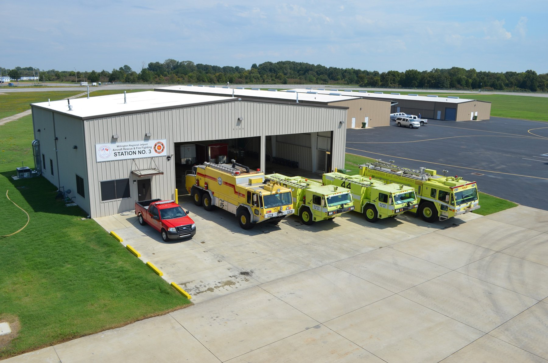Image of the Airport Fire Station with five trucks parked in front of it at the Memphis Millington Airport