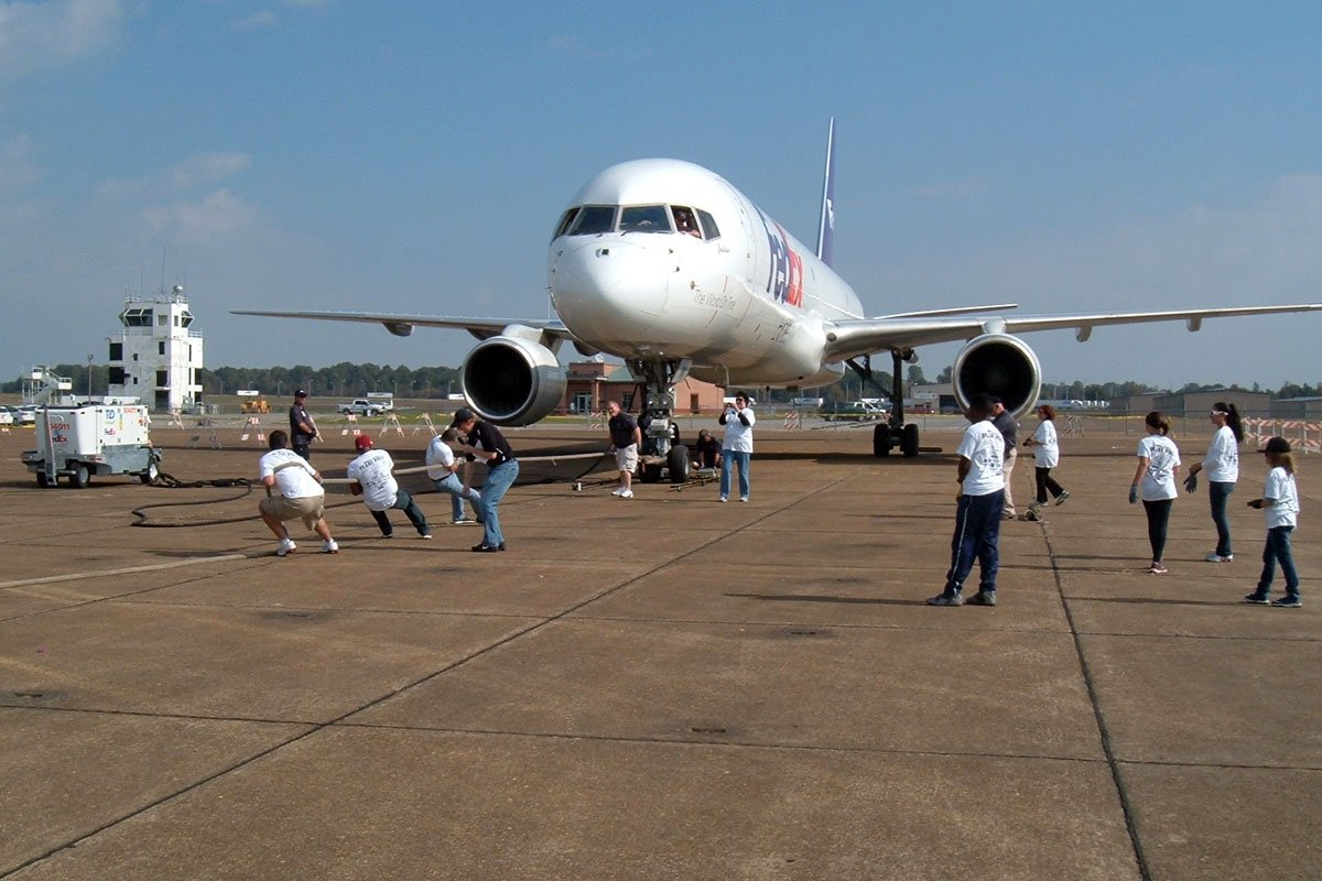 People pulling a large FedEx airplane with a rope at Memphis Millington Airport plane pull event